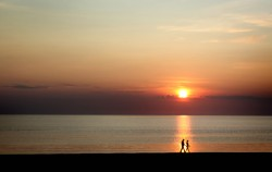 photo of two people walking on a beach at sunset