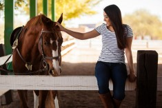 photo of a young female patient sitting on a fence petting a horse