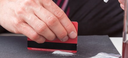 Businessman cutting cocaine to snort.