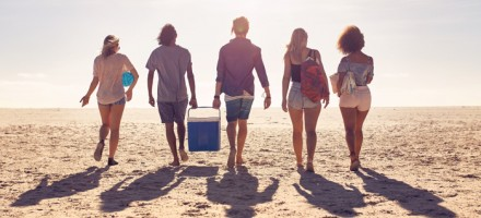photo of a group of young people gong to the beach carrying a large cooler filled with alcohol