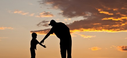 Father reaching out to help his young son