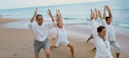Group of alcoholic patients doing yoga on the beach.