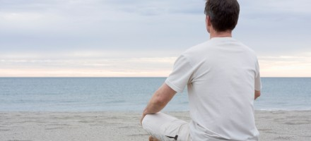 Man  at peace sitting on beach meditating.