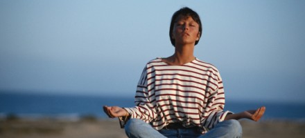 woman meditating while sitting cross legged on beach