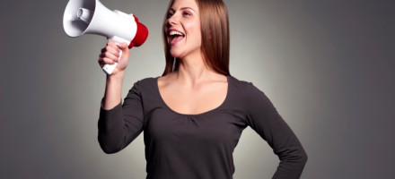 Woman shouting out her success through megaphone.